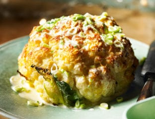 Whole roasted cauliflower with cheddar and spring onion sauce