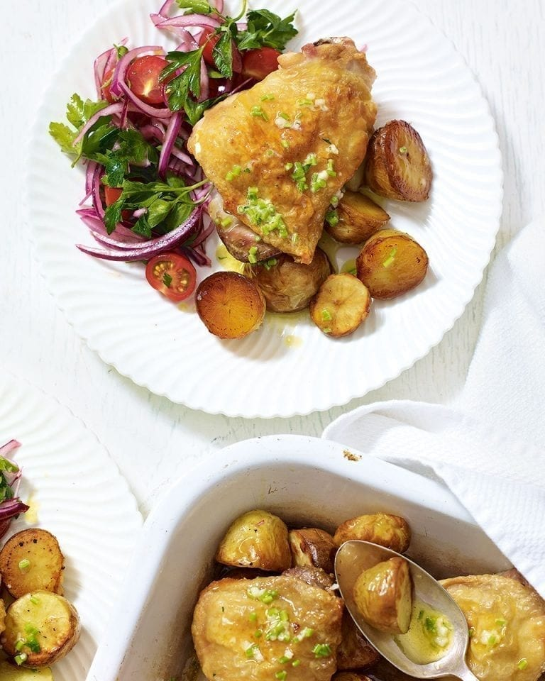 Roast chicken thighs with garlic butter potatoes and tomato salad