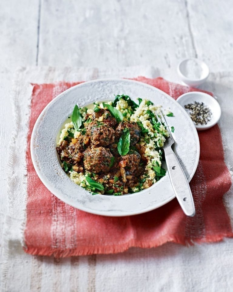 Meatballs in spinach and tomato sauce with herby couscous