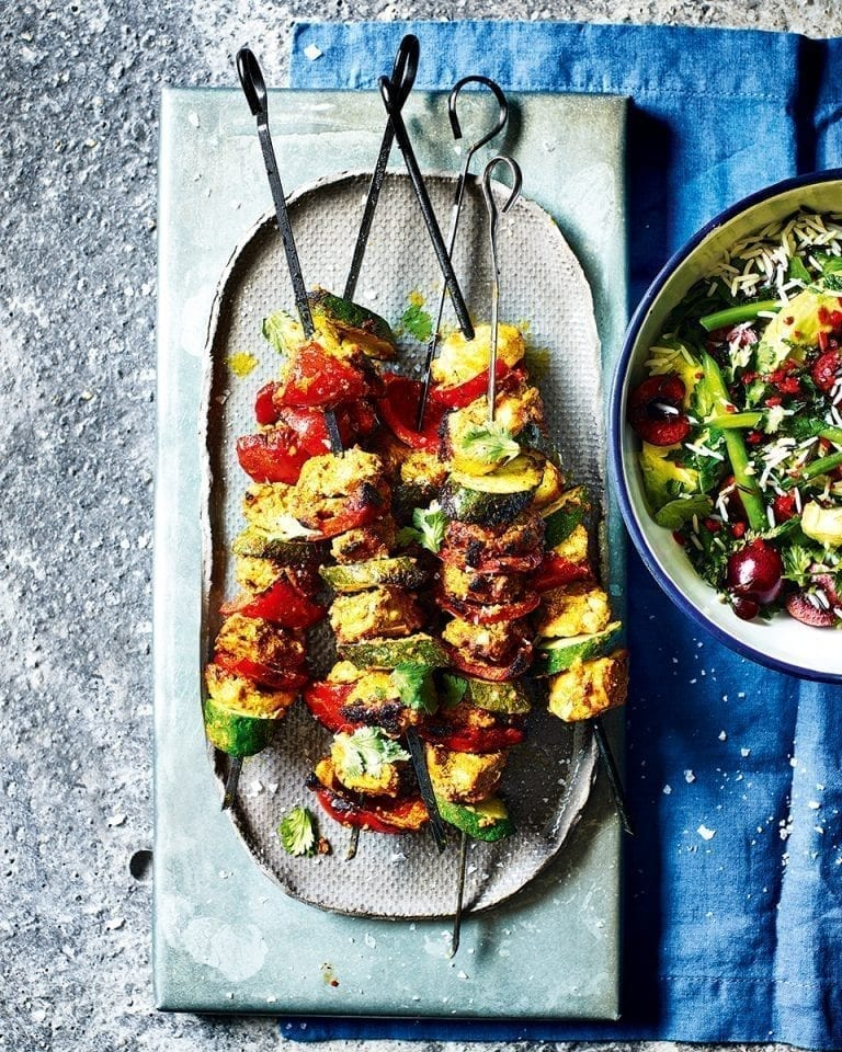 Tandoori-style chicken skewers with green rice and cherry salad