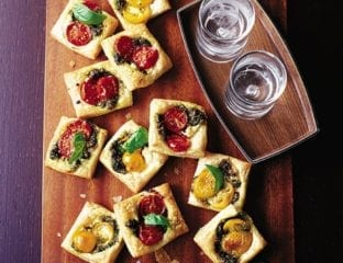 Pastry squares with goat's cheese, pesto and tomato