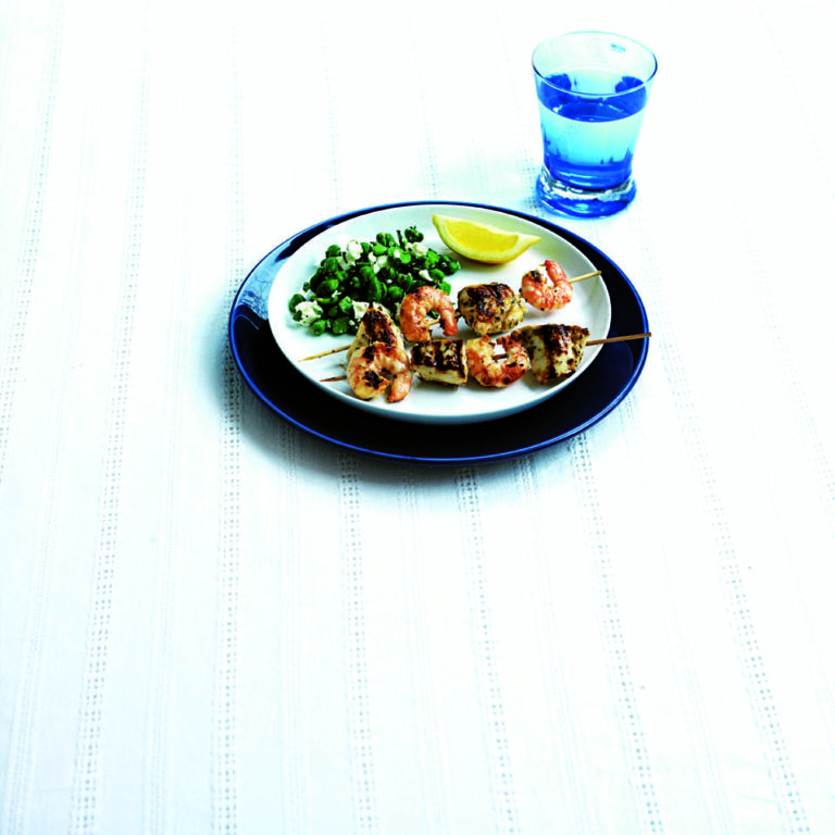 Chicken and prawn skewers on greek salad