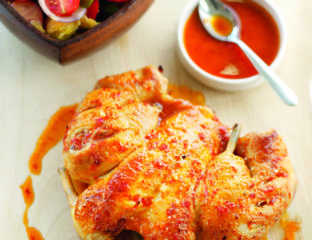 Spatchcocked roast chicken with chilli coating and tomato salad