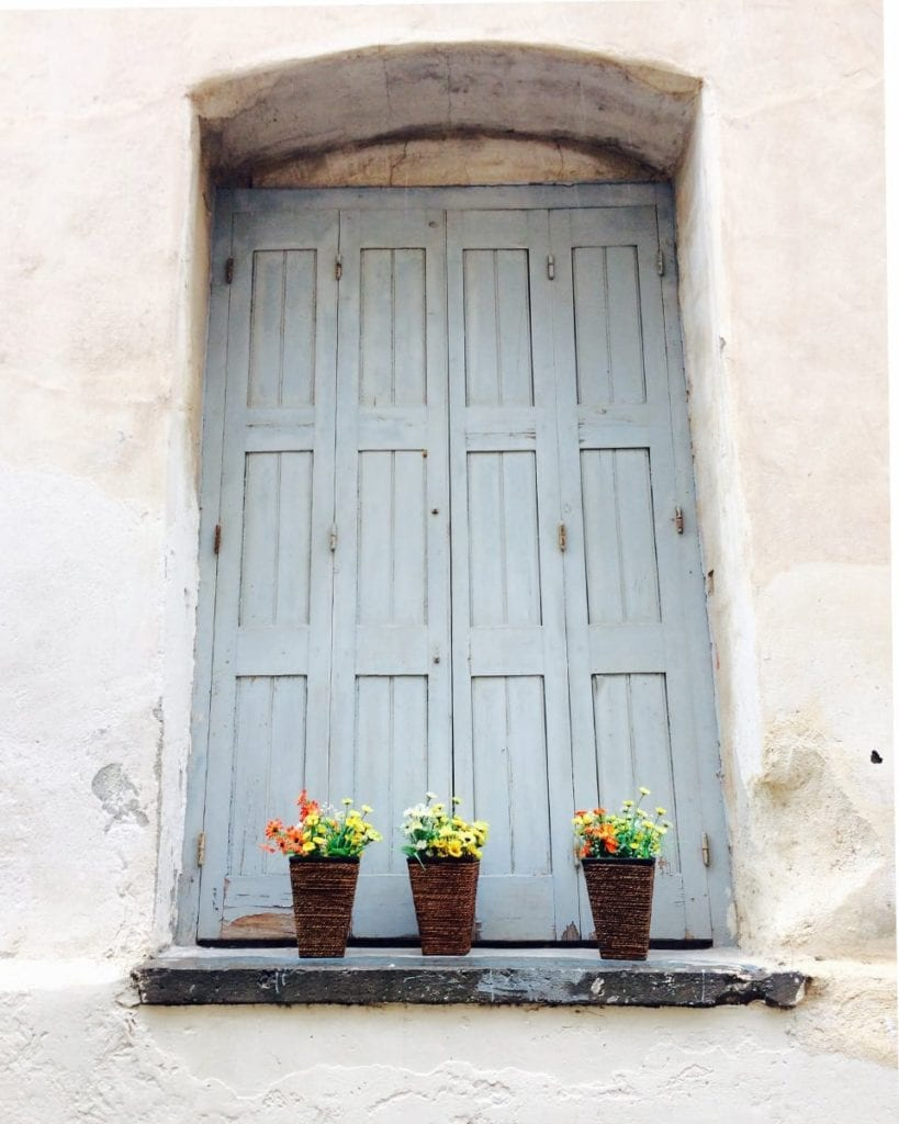Image of window with blue shutters and flowers