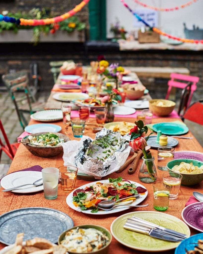 Image of large colourful tables laden with food