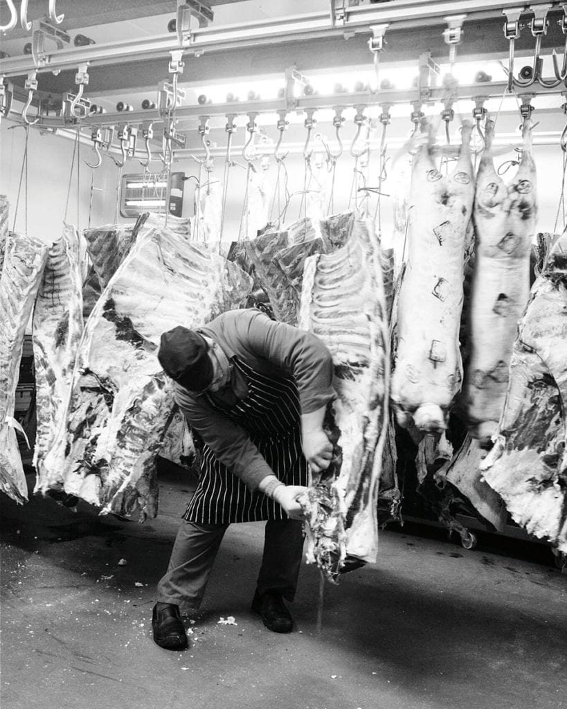 black and white image of a butcher removing meat from a carcass
