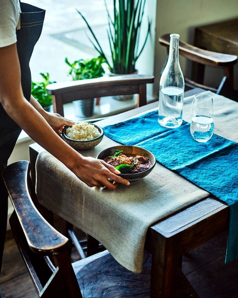 Image of a waiter placing massaman curry and rice on a table