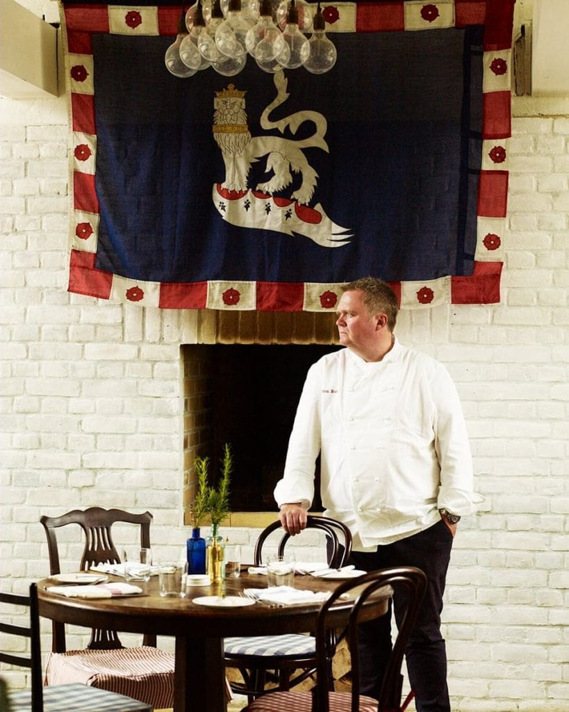 Image of chef standing at a table in the Goodwood restaurant