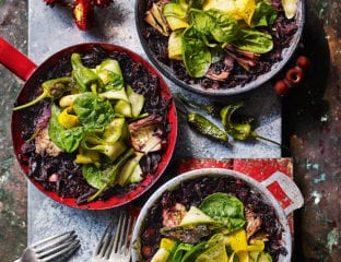 Black rice paella with artichokes, peppers and spinach
