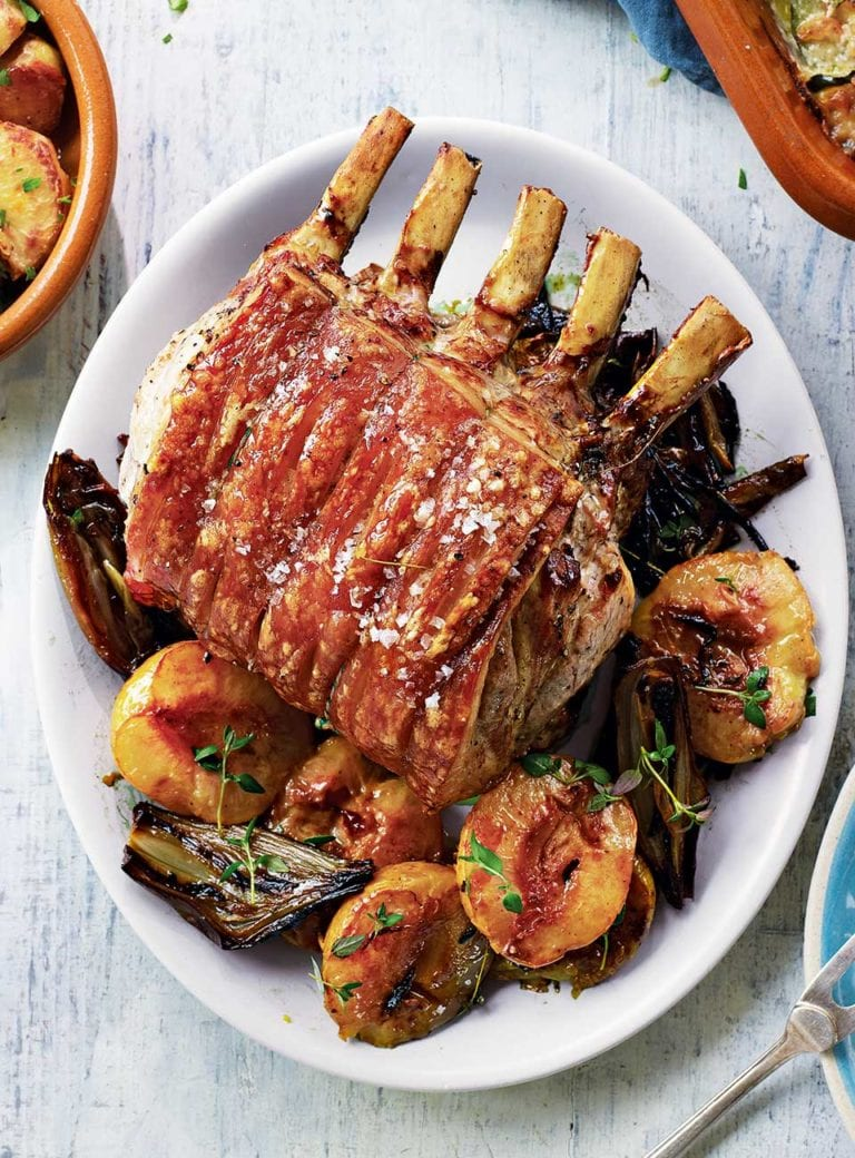 Roast pork with peaches, garlic roast potatoes and courgette gratin