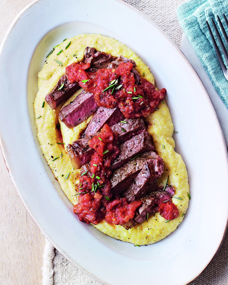 Steak with polenta and tomato and caper sauce